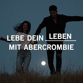 Lebe den Abercrombie-Style. Man and woman holding hands in a field at night.