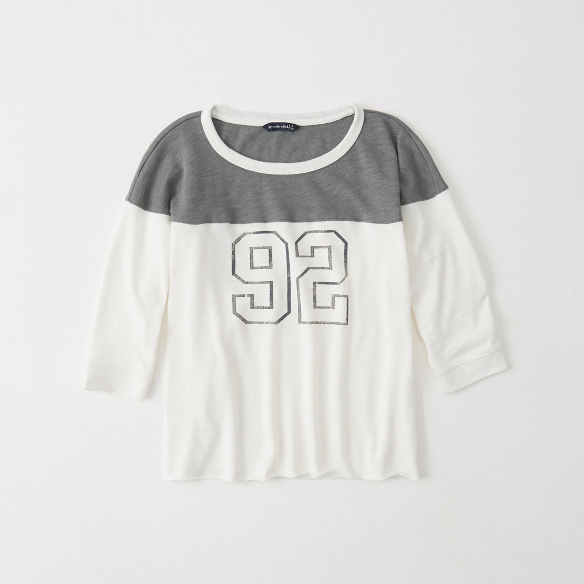 gray and white long sleeved graphic football tee.